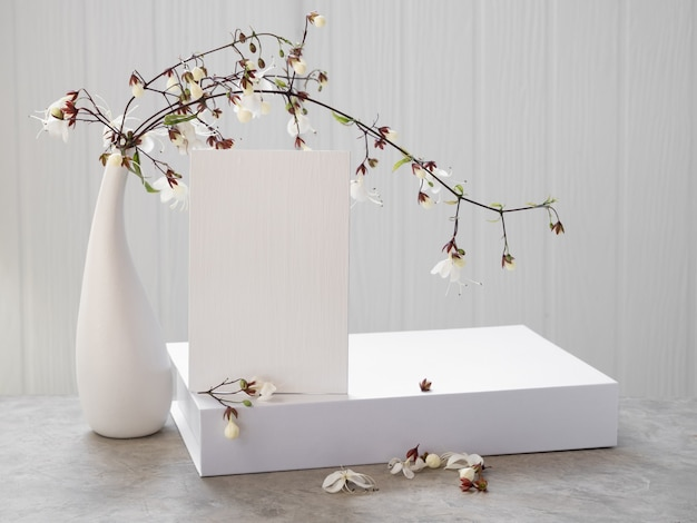 コンクリートのテーブルにセットされたモダンな花瓶に白い招待状、本、美しいうなずくクサギの花をモックアップ