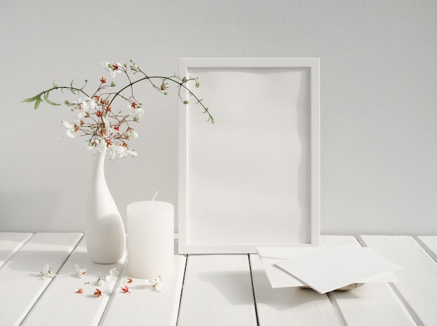 Mock up white invitation card,poster frame,candle and beautiful nodding clerodendron flowers in eramic vase on wood table white room interior,greeting card in soft tone still life