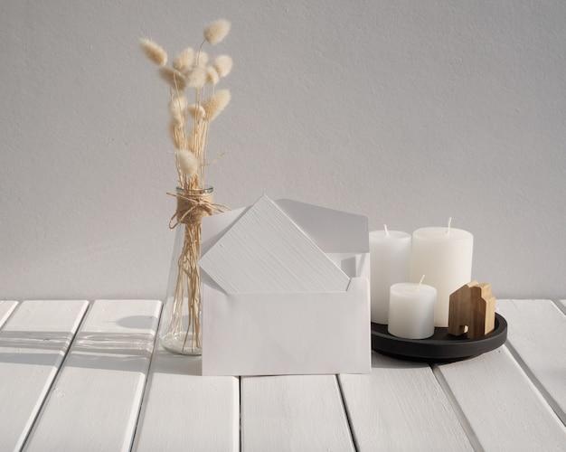白い木製のテーブルルームのインテリアにモダンなガラスの花瓶の構成で白い招待カードキャンドルとlagurusovatusドライフラワーをモックアップ