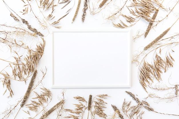 Плоский макет белой фоторамки с пампасной травой на белой стене
