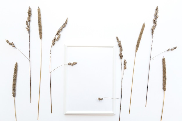 Mock up white photo frame flat lay with pampas grass on a white wall