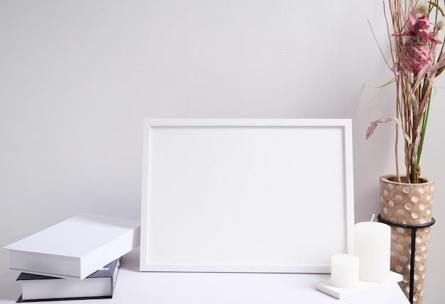 Макет белой рамки плаката, свечи, книга и красивые сушеные цветы в современной деревянной вазе над интерьером комнаты с белым деревянным столом