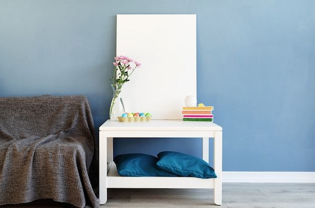 Mock up white poster frame on coffee table in blue room. white blank canvas in interior