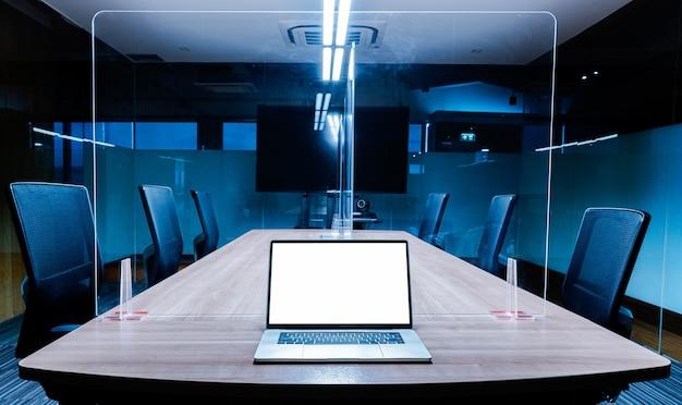 Макет ноутбука с белым экраном на столе с прозрачным акриловым листом разделяет центр на столе для переговоров, чтобы предотвратить covid-19 в конференц-зале