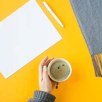 Mock up - white sheet of paper next to a cup of coffee in female hand
