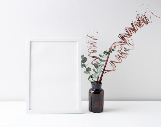 Макет белого деревянного декора в рамке для плаката с листьями эвкалипта и сухими ветками в коричневой стеклянной бутылке