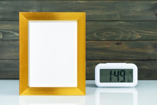 空白の金色のフレームと木製の背景を持つテーブルの上のデジタル目覚まし時計でモックアップ