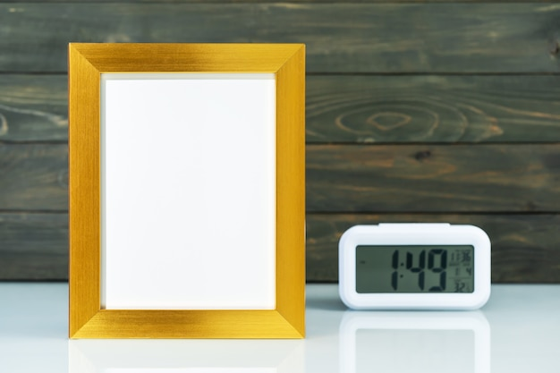 Mock up with blank golden frame and digital alarm clock on table with wood background