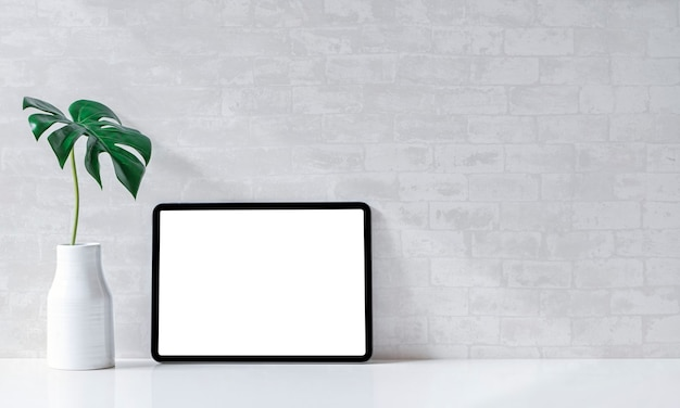 白いテーブルに空白の画面のタブレットとセラミックの花瓶を使って、ワークスペースをモックアップします。