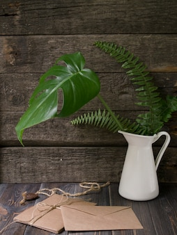 Mock up workspace with tropical leaves in vase and craft envelopes on wooden background