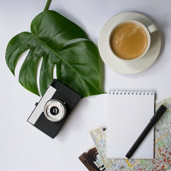 Mock up workspace with tropical palm leaf, notebook, camera, pen, card and coffee cup
