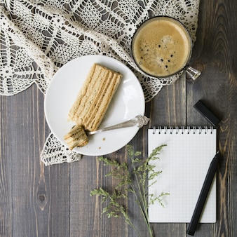 Mock up workspace with wild grass, pen, notebook, slice of the cake and cup of coffee on wooden background. flat lay, top view. stylish female concept