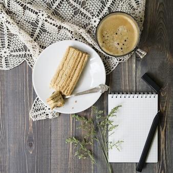 野生の草、ペン、ノート、ケーキのスライスと木製の背景の上にコーヒーを1杯のワークスペースをモックアップします。フラット横たわっていた、上面図。スタイリッシュな女性の概念