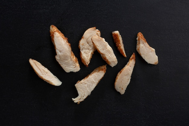 Mockeup of cooked chicken breast chunks on dark background. closeup