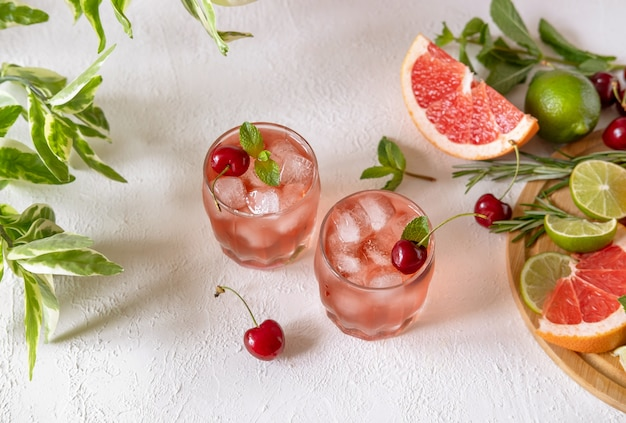 Mocktail with pink syrup and sweetened cherry