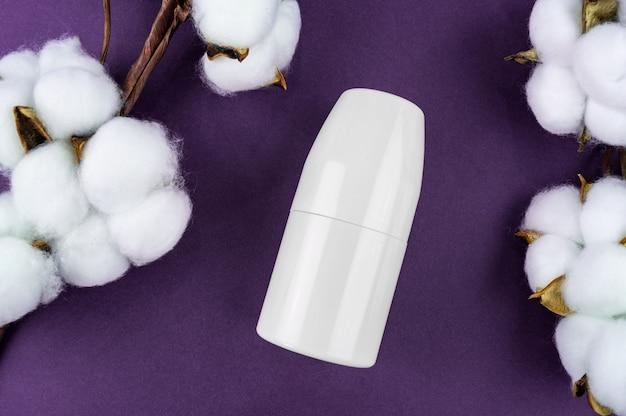 Макет антиперспирант на фиолетовом фоне. хлопок и листья являются натуральной косметикой.