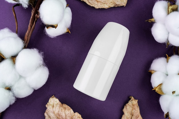 Mockup antiperspirant on a purple background. cotton and leaves are natural cosmetics.