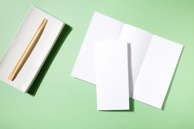 Mockup asian cuisine restaurant menu or brochure, sushi plate and food sticks on green background