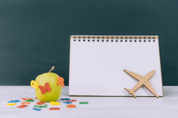 Mockup back to school. green apple with colored letters and notepad space.
