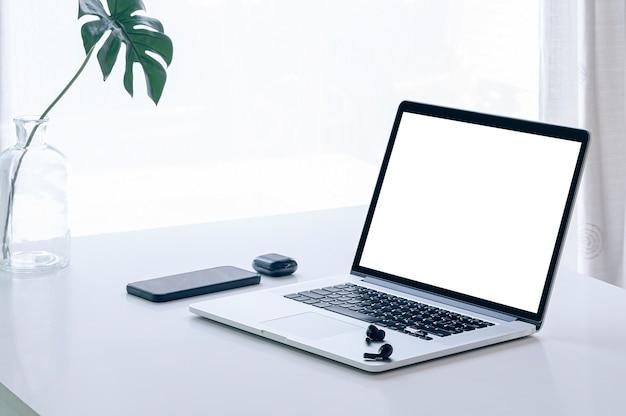 밝은 빛을 배경으로 흰색 테이블에 모형 balnk 화면 노트북 컴퓨터.