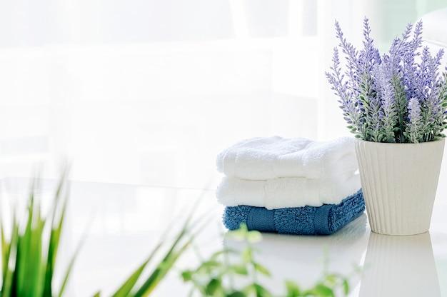 Макет банные полотенца на белом столе с комнатным растением в белой комнате