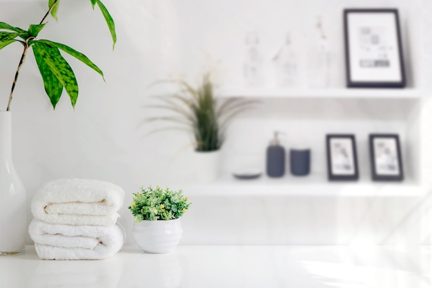 Mockup bath towels on wooden table in white room with copy space.