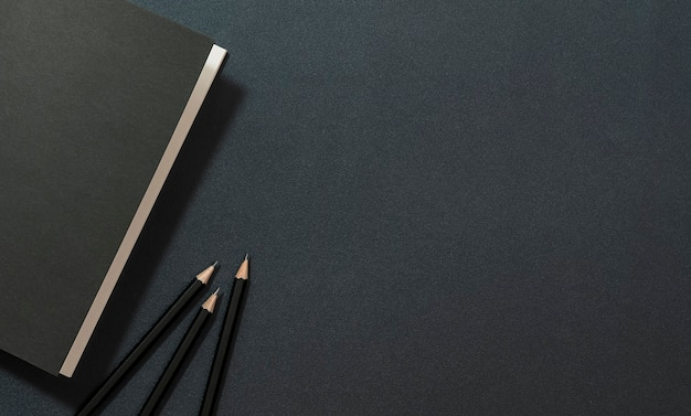 Mockup black book and pencil on black leather