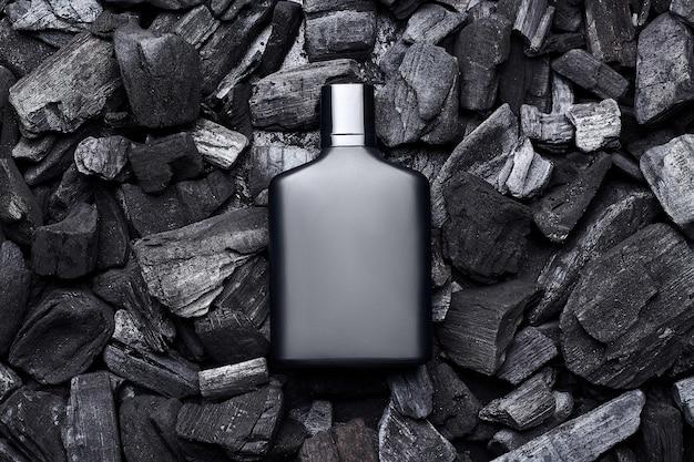 Mockup of black fragrance perfume bottle mockup on dark coals background. top view. horizontal