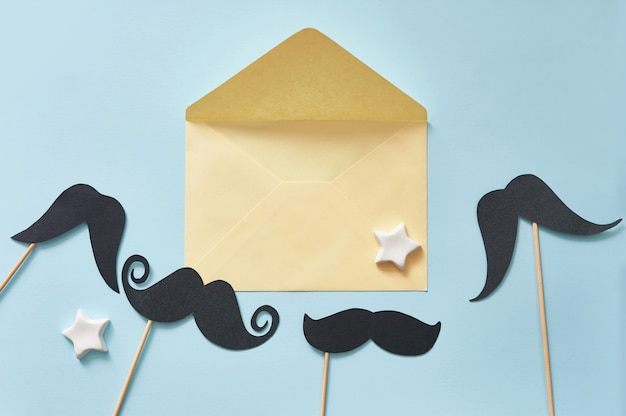 Mockup black mustaches on blue paper background and yellow envelope
