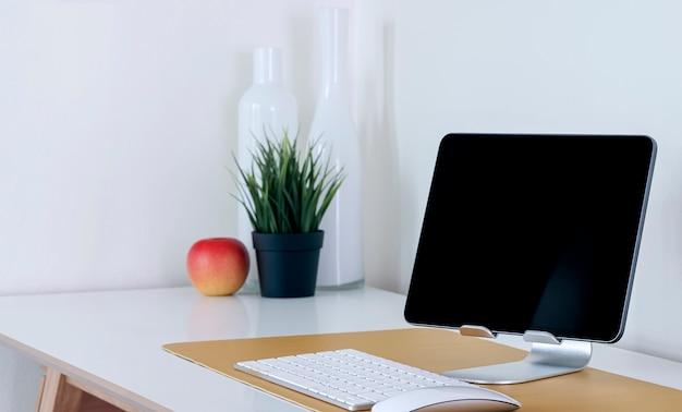 Планшет с черным экраном макета на подставке с клавиатурой, растением и яблоком на белом столе.