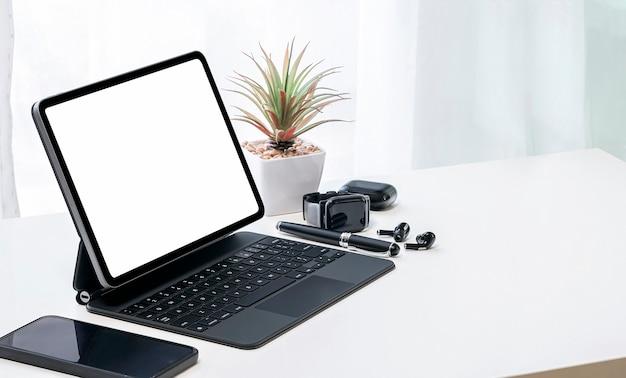 白いトップテーブルに魔法のキーボード、スマートウォッチ、イヤホンを備えたモックアップブラックスクリーンタブレット