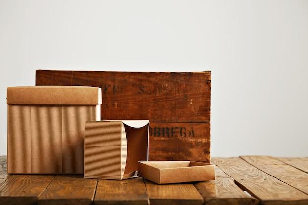 白で隔離のレトロなラフブラウンの木枠の横にあるモックアップ空白のベージュの紙箱