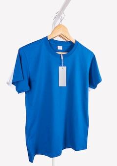 흰색 배경에 격리된 광고를 위한 빈 파란색 티셔츠와 빈 레이블 태그를 흉내냅니다.