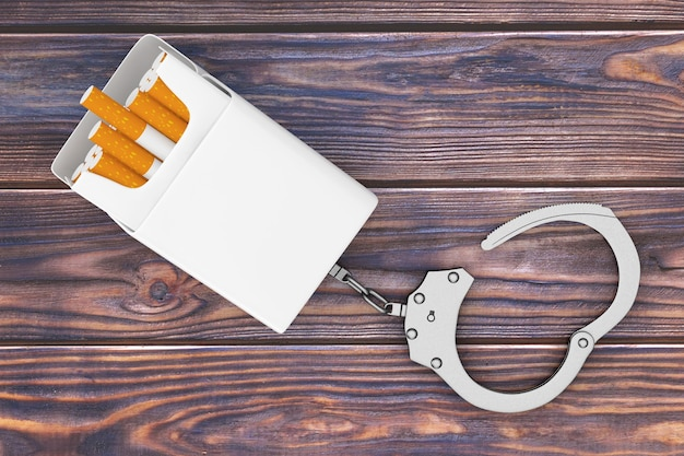 Mockup blank cigarettes pack chained to metal handcuffs on a wooden table background. 3d rendering