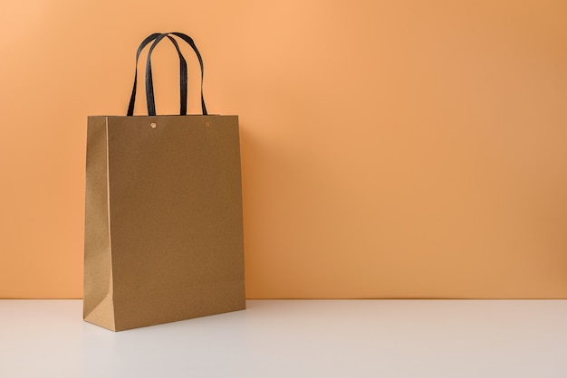 Mockup of blank craft package or brown paper shopping bag with handles