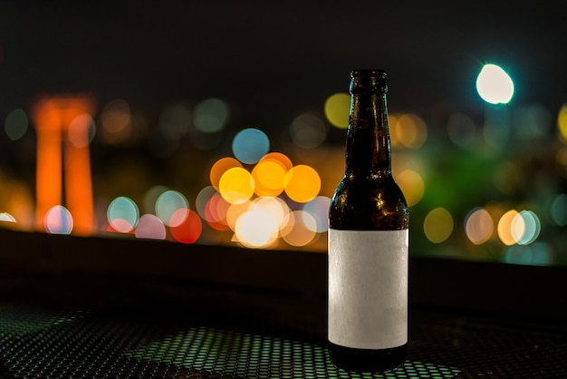 Mockup blank label cold glass bottles of beer with night light bokeh background