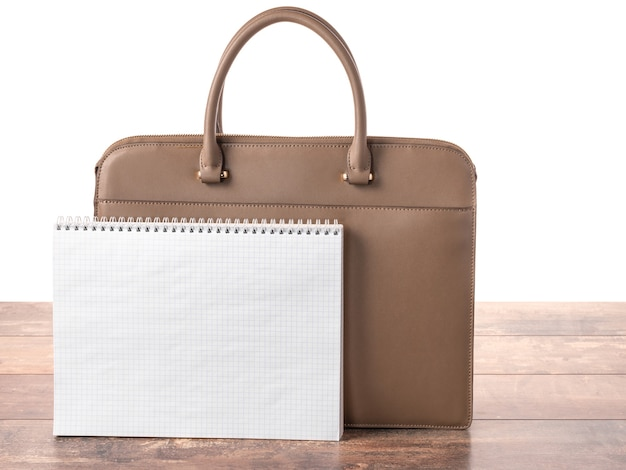 Mockup blank notebook on spiral against the background of business briefcase bag.