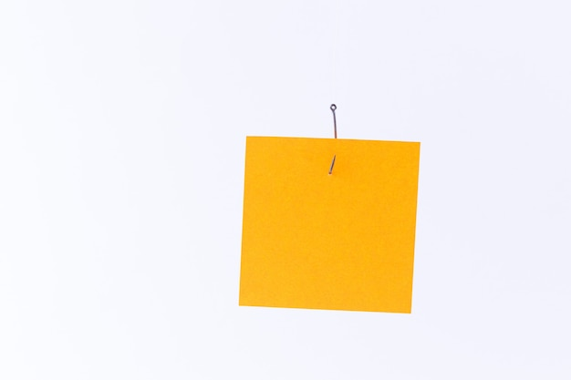 Mockup of a blank orange memo paper with copy space hanging on a fishing hook