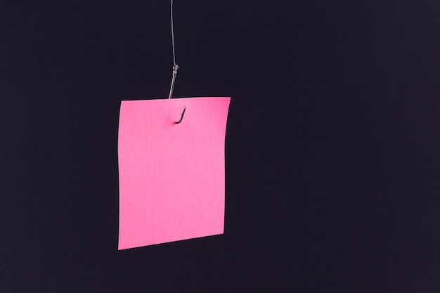 Mockup of a blank pink memo paper with copy space hanging on a fishing hook