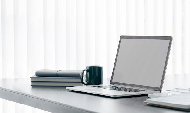 Портативный компьютер с пустым экраном макета и принадлежности на деревянном столе.