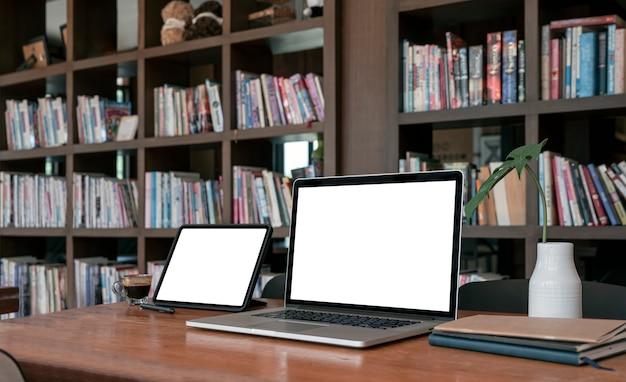 ライブラリの木製テーブルに空白の画面のラップトップコンピューターとタブレットをモックアップします。