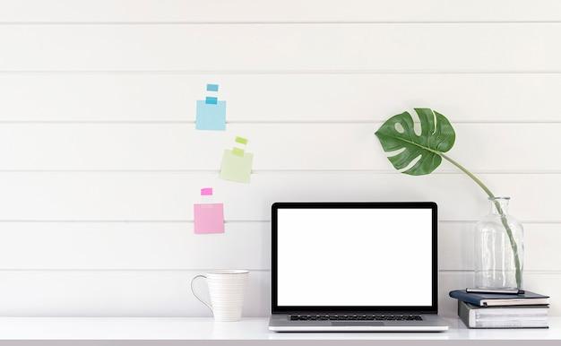Портативный компьютер с пустым экраном макета на белом деревянном столе с белым фоном стены.