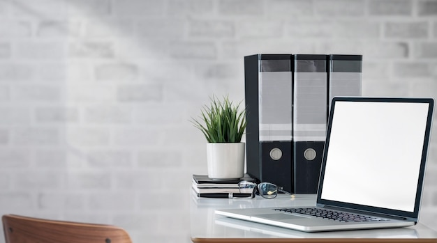 Mockup blank screen laptop computer with file folder on white table.