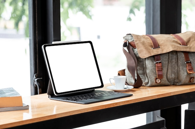 Mockup blank screen laptop with coffee cup and sling bag on wooden table in cafe room.