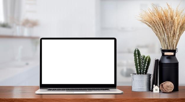 Макет ноутбука с пустым экраном и комнатным растением на деревянном прилавке