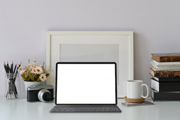 Mockup blank screen modern tablet on hipster workspace