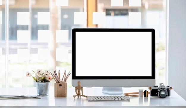 Монитор пустого экрана макета и принадлежности на белом деревянном столе.