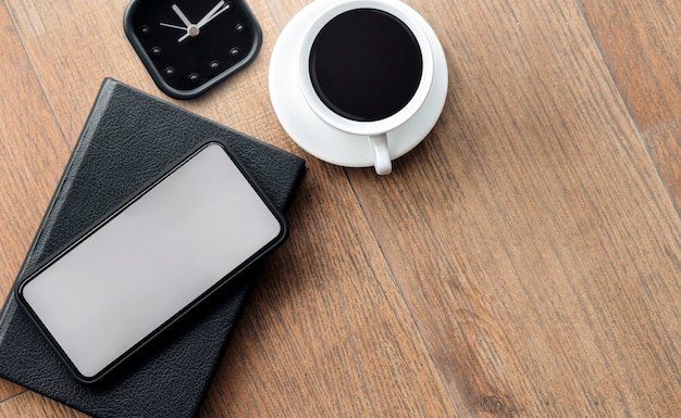 Mockup blank screen smartphone with cup of coffee and alarm clock on wooden floor