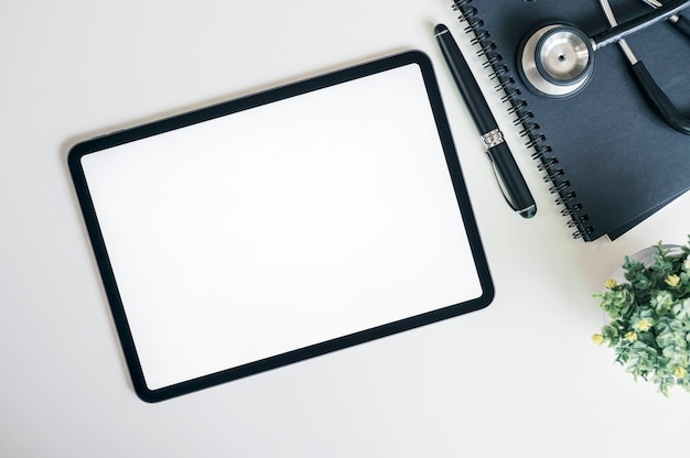 モックアップの空白の画面タブレットと白いテーブルの聴診器
