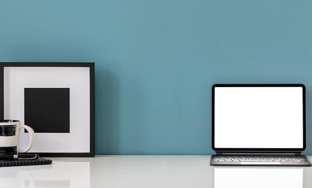 모형 빈 화면 태블릿 및 나무 액자와 파란색 벽 배경으로 흰색 테이블.